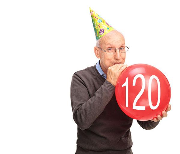 Cheerful senior blowing up a balloon
